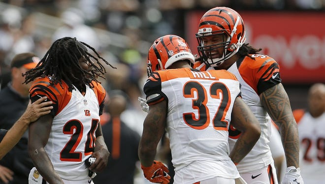 Bengals cornerback Adam Jones (left), and middle linebacker Rey Maualuga (right) congratulate running back Jeremy Hill after his touchdown run in the first quarter last week against the Oakland Raiders.