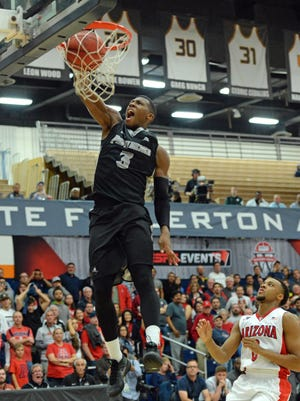 Nov 27, 2015; Fullerton , CA, USA; Providence Friars guard Kris Dunn (3) dunks the final two points of a 69-65 win as Arizona Wildcats guard Parker Jackson-Cartwright (0) defends during the second half at Titan Gym.