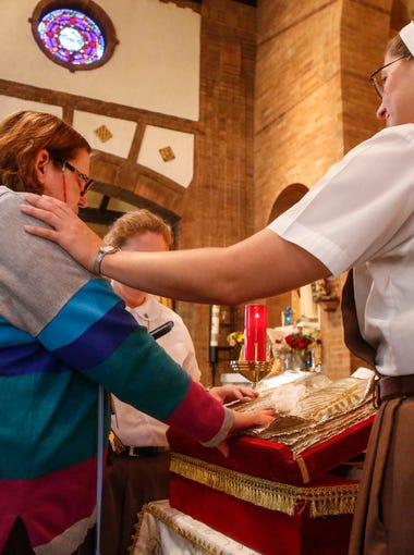Sister Grace Marie of the Servants of the Pierced Heart of Jesus and Mary in Miami, Florida, right, places her hand on the shoulder of Debbie Forrest of Beaverdale as they pray before relics of Pope John Paul II on Thursday, Sept. 7, 2017, at St. Anthony Catholic Church in Des Moines.