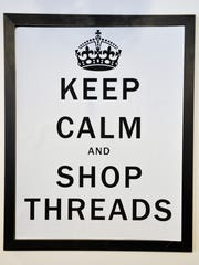 A sign tells customers to keep calm and shop at Threads.