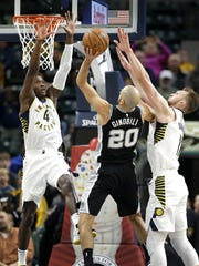 Pacers guard Victor Oladipo (4) and Domantas Sabonis (11) team up on defending San Antonio guard Manu Ginobili (20), Oct. 29, 2017.