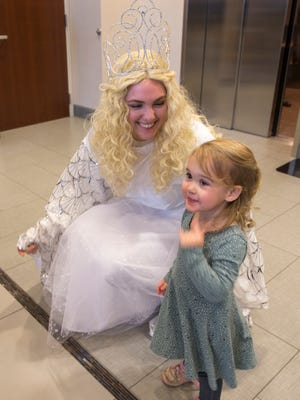 Macy Duncan, 17, Carmel, visits with Lena Rutemoeller, 2, Brownsburg, who is smiling after seeing Duncan's outfit during a preview of a new German-themed Christmas market located in Carmel that opens on Saturday, Nov. 18, closes on Christmas Evening, and includes a variety of food and gift items, Carmel, Monday, Nov. 13, 2017.
