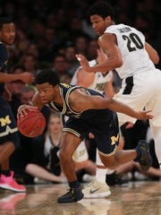 Michigan guard Zavier Simpson steals the ball from
