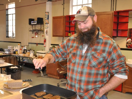 Travis Young cooks homemade scrapple on Saturday during