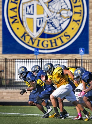 The Marian University Knights football team runs sprints across the field during practice at the Indianapolis school on September 25, 2014.