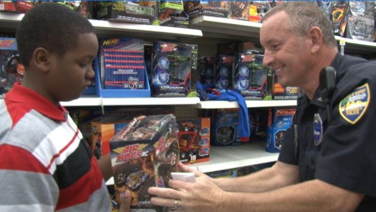 JSO Detective Carl Graham hands a child a toy