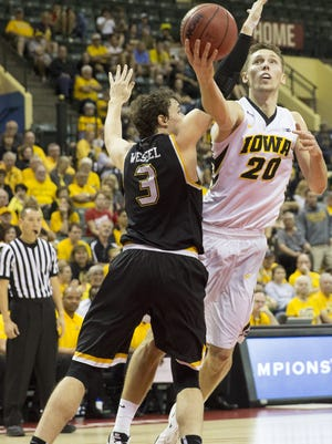 Iowa forward Jarrod Uthoff (20) lays up the ball against Wichita State guard Evan Wessel (3) during the first half of an NCAA college basketball game Sunday, Nov. 29, 2015, in Orlando, Fla. (AP Photo/Willie J. Allen Jr.)