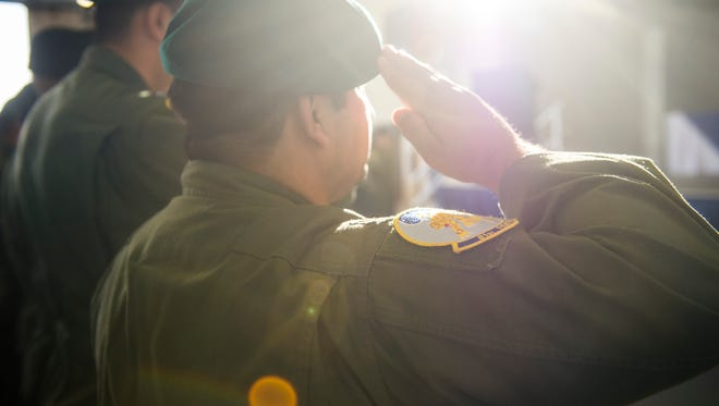 An Afghan air force pilot salutes during the playing of the Afghan national anthem at the graduation of the first 81st Fighter Squadron's student pilot class Dec. 18 at Moody Air Force Base, Georgia. The 81st FS graduated eight Afghan air force students trained as combat ready attack pilots on the A-29 Super Tucano.