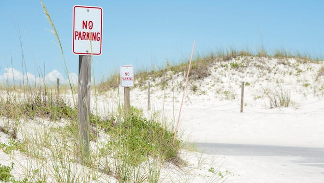 Signs marking no parking areas along Johnson's Beach on Perdido Key, FL on Thursday, June 23, 2016.  The National Park Service is working to improve parking , crossovers, and other public access using restitution money from the BP oil spill.