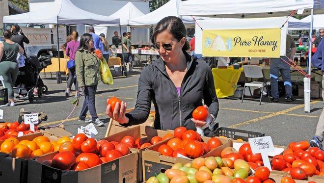 Liz Fassler chooses tomatoes at the Ramsey Farmer's Market.