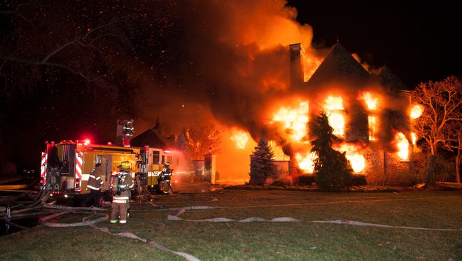 Firefighters battle a four-alarm fire at a home on Childs Point Road, early Monday, Jan. 19, 2015, in Annapolis, Md. The occupants of the home were unaccounted for and fire officials were investigating.