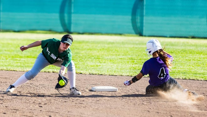 El Diamante shortstop Janelle Tumacder, left, attempts to tag Mission Oak's Drew Torres at second base on Tuesday in a non-league softball game in Visalia.