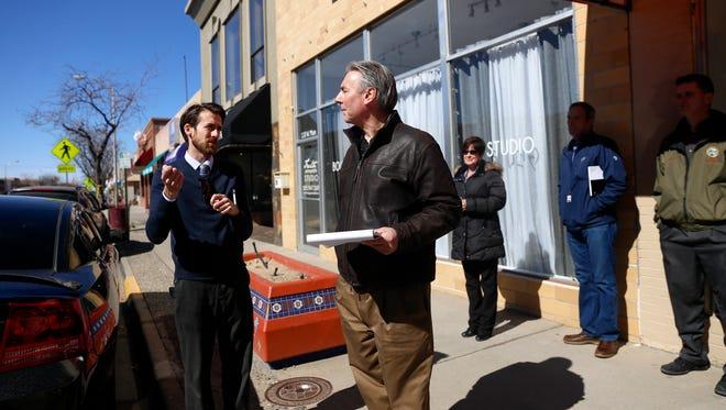 Warren Unsicker, left, CEO of Four Corners Economic Development, talks with Scott Day of Urban Development Services during a walking tour of downtown Farmington on Monday