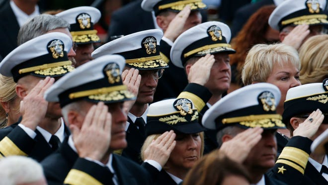Navy personnel salute during the playing of taps at a memorial service Sunday for the victims of the Washington Navy Yard shooting.
