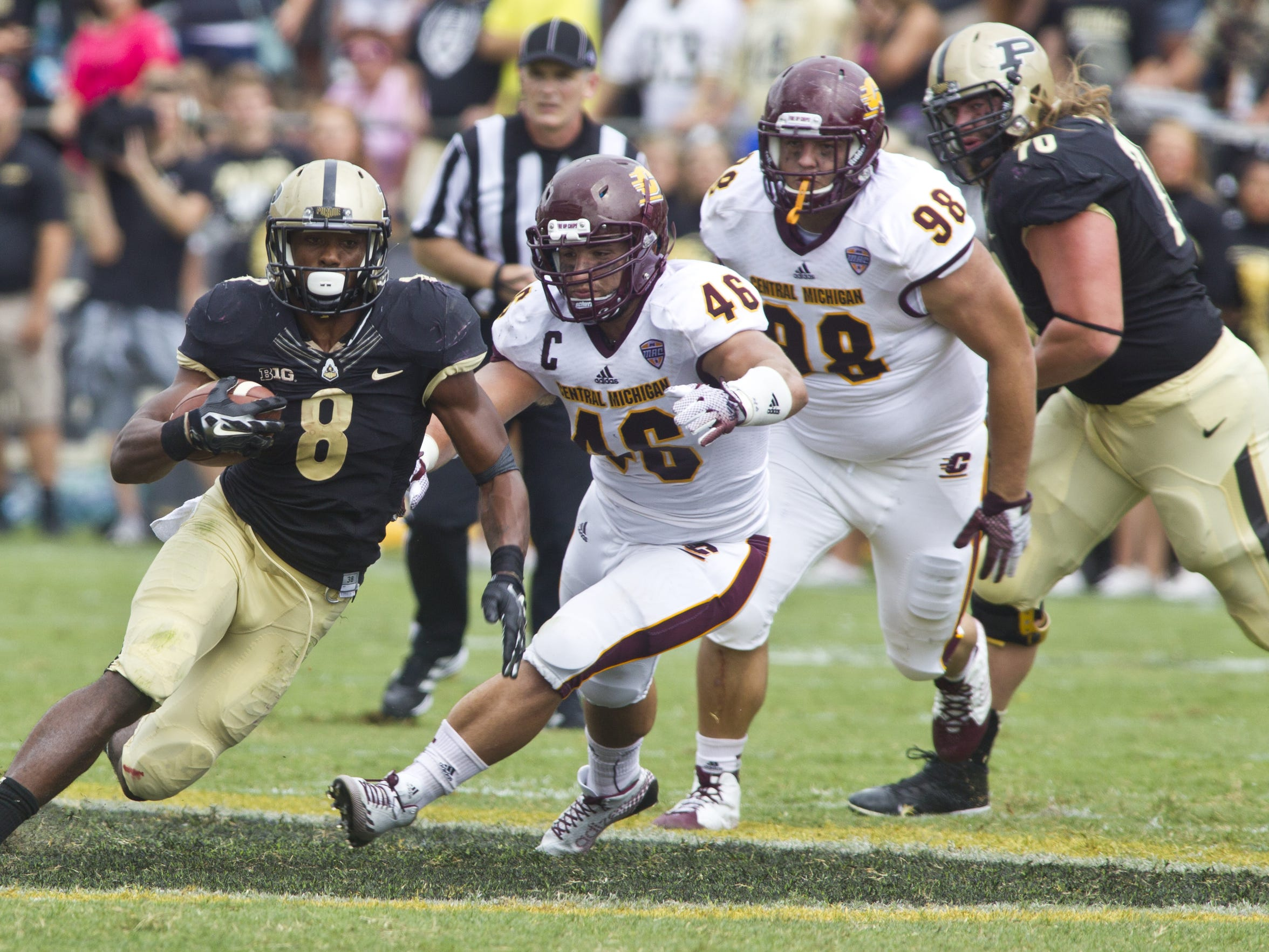 Purdue's Raheem Mosert out runs Central Michigan's Justin Cherocci (46) as Kelby Latta (98) gives chase on Saturday in West Lafayette. CMU won the game, 38-17.