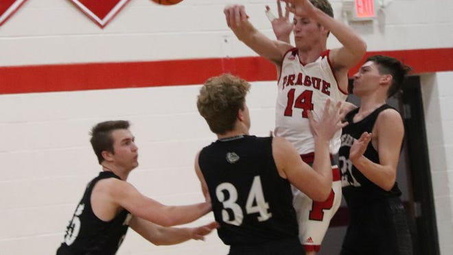 Prague's Trip Davis (14) fires off a pass while being triple-defended by Meeker's Levi Watham (left), Zack Cook (34) and Cade Patterson (21) during action Monday night in the 66 Conference Tournament at McLoud.      PHOTO BY BRIAN JOHNSON