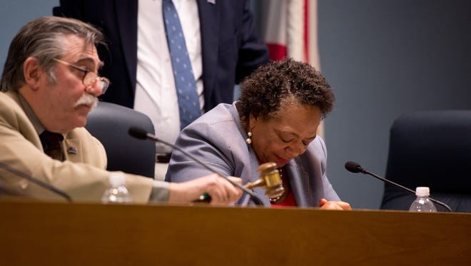 "Stuart City Commissioner Eula Clarke (center), who earlier resigned as mayor, bows her head as newly-appointed Mayor Tom Campenni calls for order during a public comment session at a city commission meeting Wednesday, Feb. 1, 2017, at Stuart City Hall. The meeting was held to determine whether to investigate further after Clarke used the term ""pig"" in front of a Stuart police officer at a local grocery store in January."