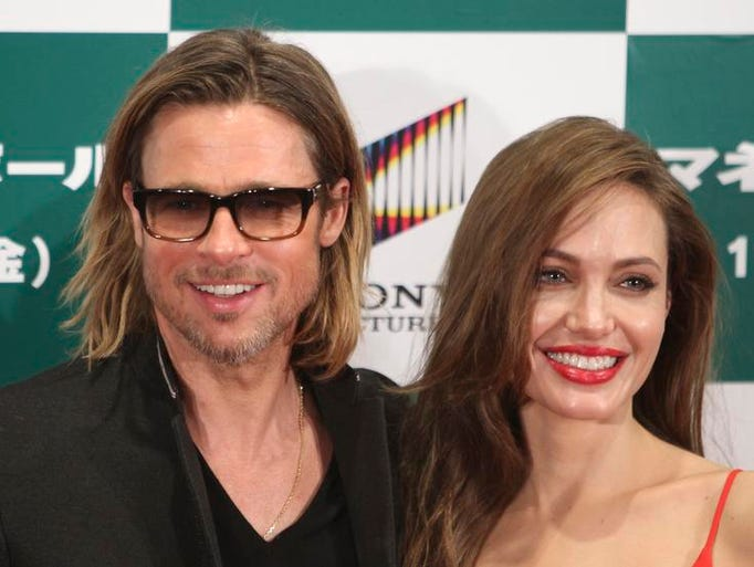 "Actors Brad Pitt and actress Angelina Jolie smile prior to the Japan premiere for his film ""Moneyball"" in Tokyo Wednesday, Nov. 9, 2011."
