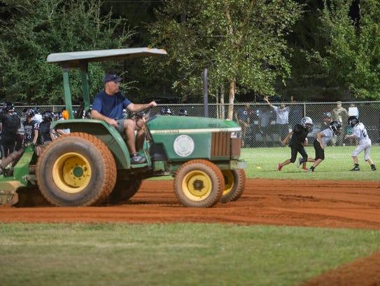 Volunteer James Hawley tills a baseball infield as