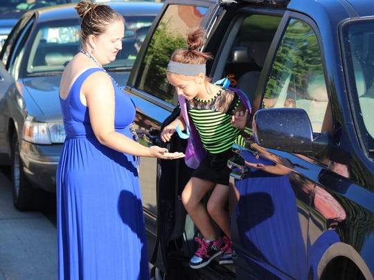 Kindergarten teacher Katie Bogan helps a student exit