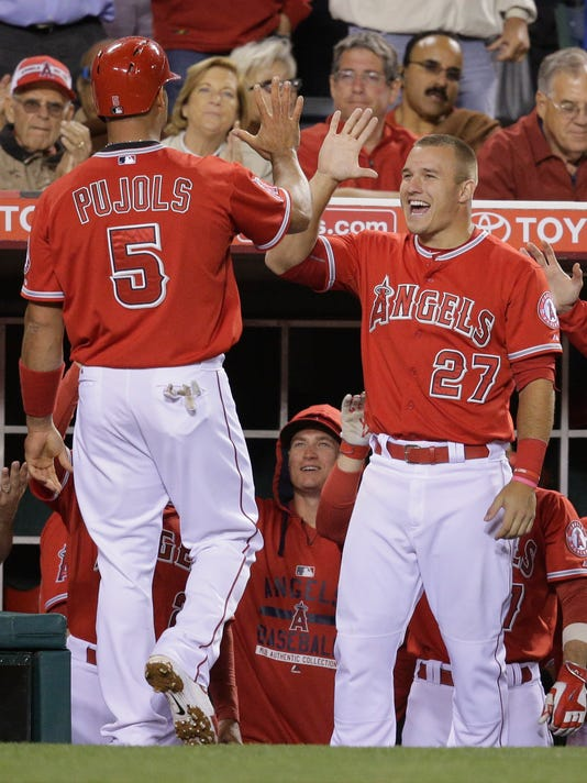 Los Angeles Angels' Albert Pujols, left, is greeted by Mike Trout after he scored on a single by Johnny Giavotella during the eighth inning of a baseball game against the Colorado Rockies, Tuesday, May 12, 2015, in Anaheim, Calif. (AP Photo/Jae C. Hong)