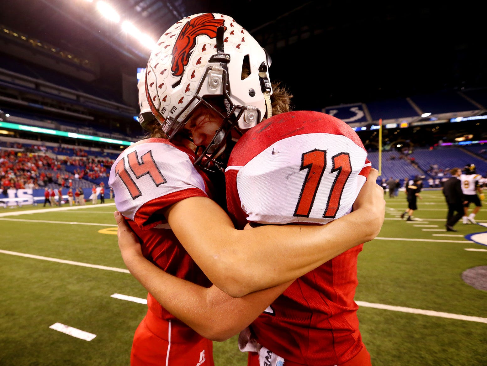 New Palestine's Zach Neligh (14) comforts quarterback Alex Neligh (11) after a tough loss in the Class 5A IHSAA Football State Tournament finals against Fort Wayne Snider at Lucas Oil Stadium on Nov. 27, 2015.