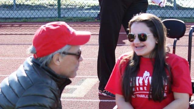 Jon Bon Jovi talks with East West Shrine Game patient ambassador Leigh Dittman.
