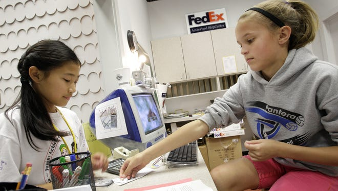 Tiffany Xie, 11 yrs, (left) and Laura Dakich, 12 yrs, (right) work at the mock Fed Ex station at the camp. Dozens of elementary students from Central Indiana are working as CEOs, loan officers and sales managers during a weeklong BizCamp offered through Junior Achievement on Keystone Ave in Indianapolis, IN. The students spend their morning creating a business plan for their invention, and they learn about financial literacy and entrepreneurialism by working in various job positions during the afternoon. JA converted a former hardware store into a business community, complete with banks, various businesses and a city hall. Here we photograph the camp on Friday, July 17, 2009. (Sam Riche / The Indianapolis Star) <b>07/20/2009 - A06 - MAIN - 1ST - THE INDIANAPOLIS STAR</b><br />Learning: Eleven-year-old Tiffany Xie (left) and Laura Dakich, 12, work at the mock FedEx station at the BizCamp conducted by Junior Achievement of Central Indiana.