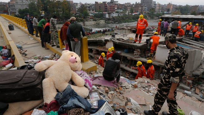 A teddy bear lies on the top of debris as Indian rescue workers look for survivors and bodies trapped in a building in Katmandu.