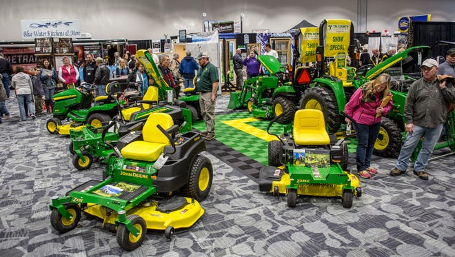 People look over a John Deere display area during the Home, Sport and Garden Show Saturday, March 19, 2016 at the Blue Water Area Convention Center.