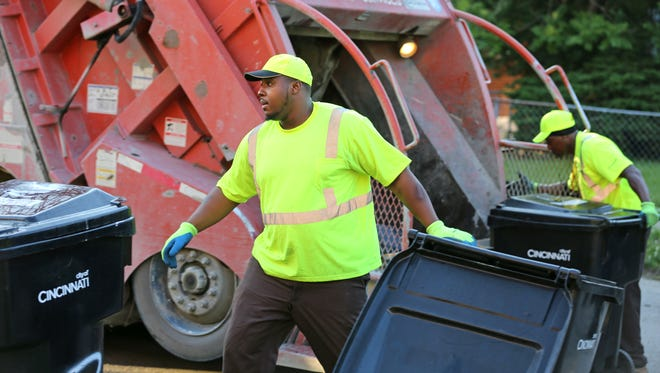 Dossie Washington, with the City of Cincinnati Sanitation Department empties garbage bins on Northdale Place in Kennedy Heights. At right is William Jackson.