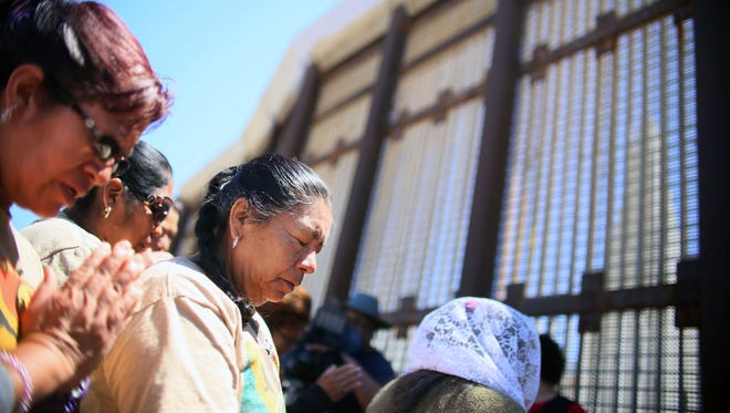 Worshipers engage in a bi-national Easter mass along the US-Mexico border fence at Friendship Park in San Ysidro, Calif.
