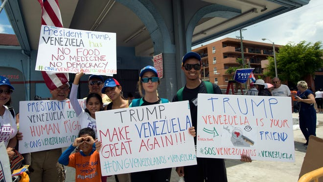 "Andreina Kissane, organizer at ONG Venezolanos por Venezuela, holds a ""Make Venezuela Great Again"" poster."