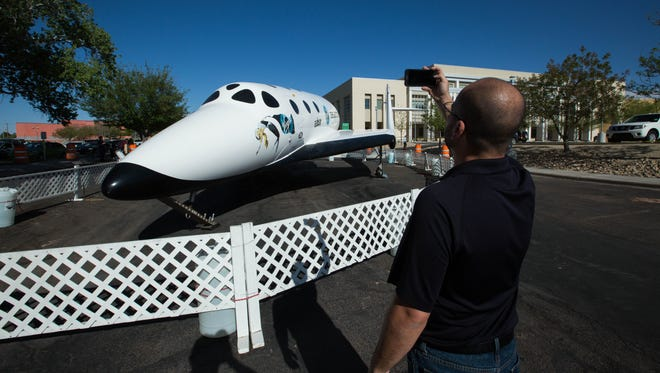 Sergio Salinas, with Visit Las Cruces, snaps a few photos Thursday April 5, 2018, of the Virgin Galactic SpaceShipTwo replica that will be on display in front of the Las Cruces City Hall for up to the next six months.