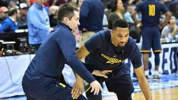 Michigan assistant coach Billy Donlon guards Zak Irvin, right, during the Michigan workout Wednesday.