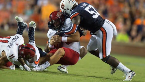 Auburn linebacker Deshaun Davis (57) tackles Arkansas