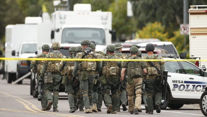 A Mesa police SWAT team walks down South Longmore Road searching for a gunman on March 18, 2015, in Mesa.