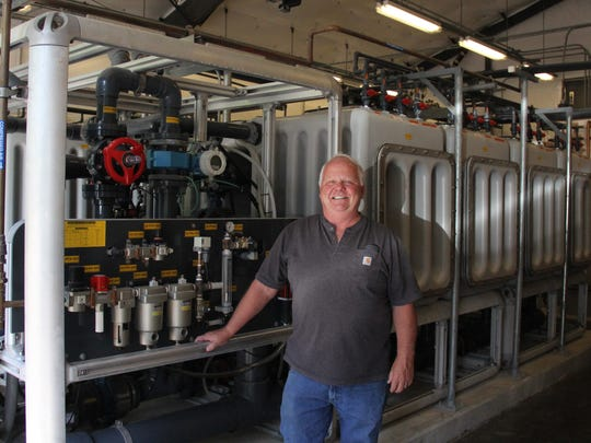 Greg Benthin, the public works superintendent for the City of Gates, poses in front of the trains of the city's membrane water filtration system.