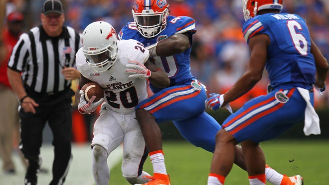 Marcus Clark of the Florida Atlantic Owls is knocked out of bounds by Jarrad Davis of the Florida Gators at Ben Hill Griffin Stadium in Gainesville.
