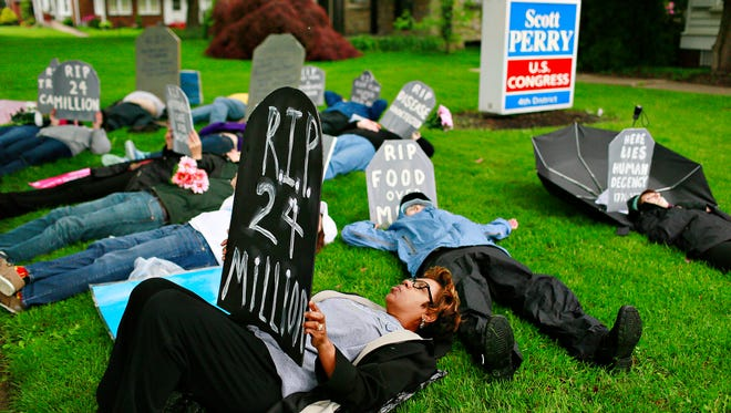 A die-in is staged by anti-Trump demonstrators outside of Congressman Scott Perry's office in Springettsbury Township, Thursday, May 11, 2017. Dawn J. Sagert photo