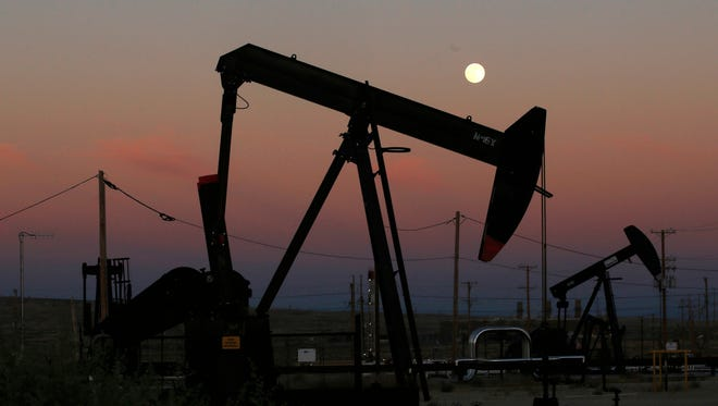 Oil derricks are busy pumping as the moon rises near the La Paloma Generating Station in McKittrick, Calif. in this file photo. The U.S. is on pace to leapfrog both Saudi Arabia and Russia as the world's biggest oil producer. (AP Photo/Gary Kazanjian, File)