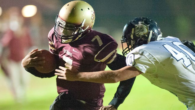 Doss Dragons quarterback Tre Taylor runs the ball in for a touchdown as Fairdale Bulldogs defensive end Adriel Robinson is too late to make the play as Doss takes on Fairdale at Doss.24 October 2014