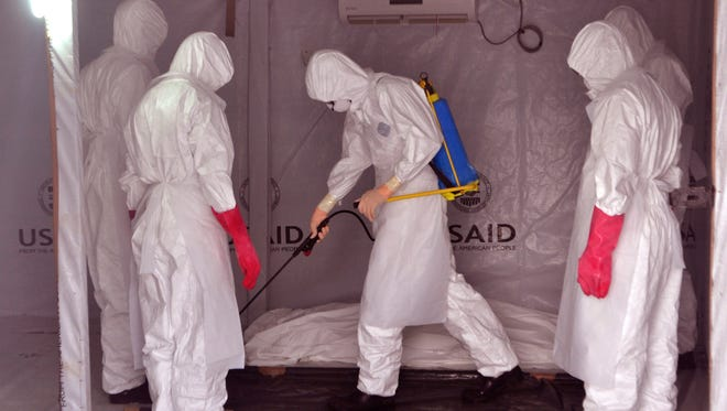 In this photo taken on Friday, Nov. 28, 2014, health workers wearing Ebola protective gear spray the shrouded body of a man with disinfectant  as they suspect he died from the Ebola virus, at a USAID, American aid Ebola treatment center at Tubmanburg on the outskirts of  Monrovia, Liberia.