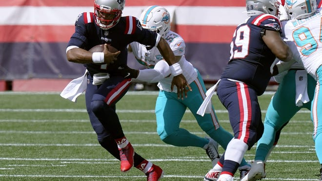 New England's Cam Newton, front, runs from Miami linebacker Kyle Van Noy in the first half of Sunday's win over the Dolphins.