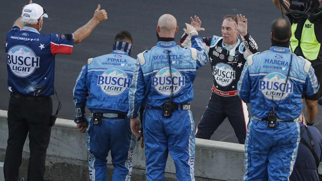 Kevin Harvick, on far side of wall, celebrates with his crew after winning the NASCAR race at Indianapolis Motor Speedway last Sunday.