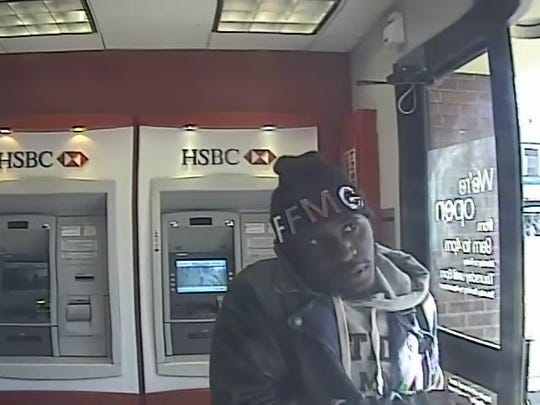 Anthony Davis deposits a stolen and fraudulently endorsed money order at an ATM. He was one of two Bronx men convicted Tuesday in an identity-theft ring targeting bank customers.