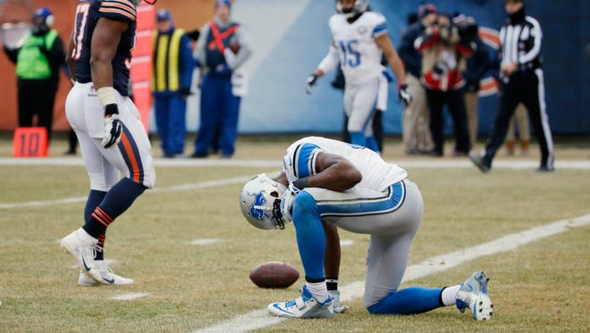 Detroit Lions wide receiver Calvin Johnson, right, kneels in the end zone after missing a catch against the Chicago Bears on Dec. 21, 2014, in Chicago.