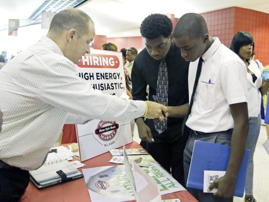 In this Wednesday, June 10, 2015 file photo, Mario Polo, of Boston Market, left, talks to job seekers Herby Joseph, right, and Kingsly Jose, center, at a job fair in Sunrise, Fla. On Labor Day weekend 2015, the U.S. job market has found an old sweet spot: 5.1 percent unemployment. Itís the lowest rate in more than seven years, suggestive of healthy hiring levels that have traditionally fostered rising incomes, consumer spending and economic growth.