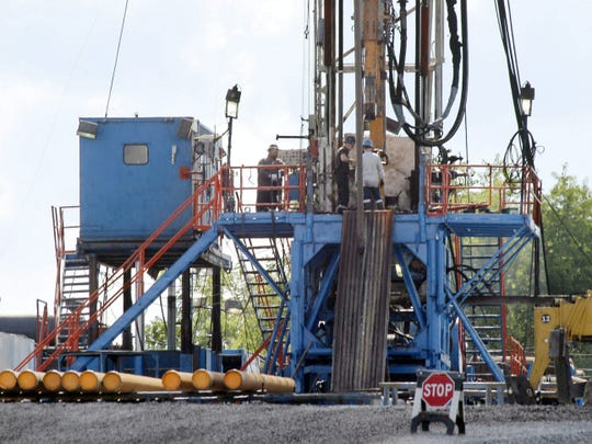 In this file photo, a crew works on a gas drilling rig at a well site for shale based natural gas in Zelienople, Pa.