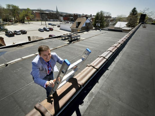 Josh Hankey climbs to the top of the Bond building, which could be renovated to add a roof deck. The Royal Square Development president and CEO is heavily invested in the revitalization of downtown York City.